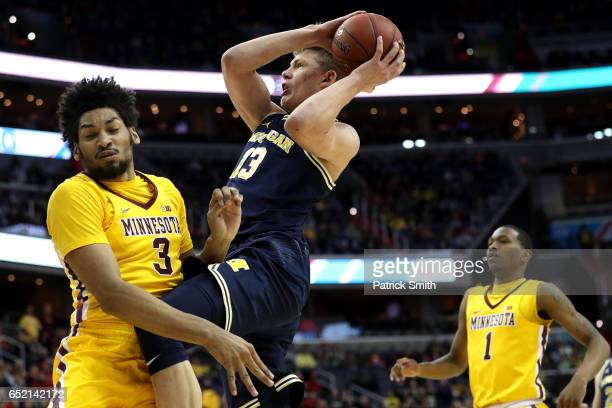 Moritz Wagner of the Michigan Wolverines shoots in front of Jordan Murphy of the Minnesota Golden Gophers during the first half in the semifinals of...