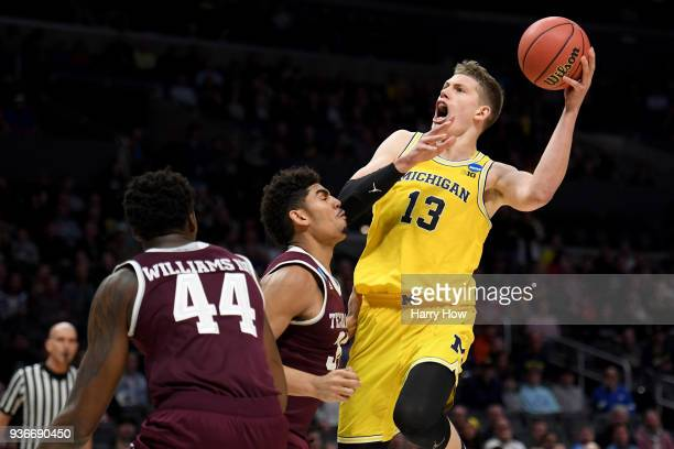 Moritz Wagner of the Michigan Wolverines shoots over Tyler Davis of the Texas AM Aggies in the first half in the 2018 NCAA Men's Basketball...