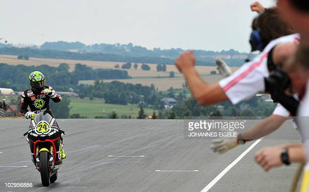 Moriwaki rider Toni Elias of Spain celebrates his victory on the racetrack of the Moto2 race of the Moto Grand Prix of Germany at Sachsenring Circuit...