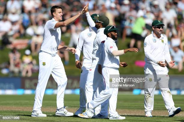 Morne Morkel of South Africa celebrates with team mates the dismissal of Jimmy Neesham of New Zealand during day three of the First Test match...