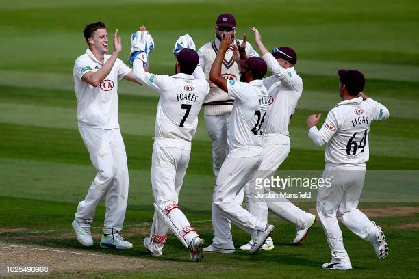 Morne Morkel of Surrey celebrates with his teammates after dismissing Samit Patel of Nottinghamshire during day three of the Specsavers County...