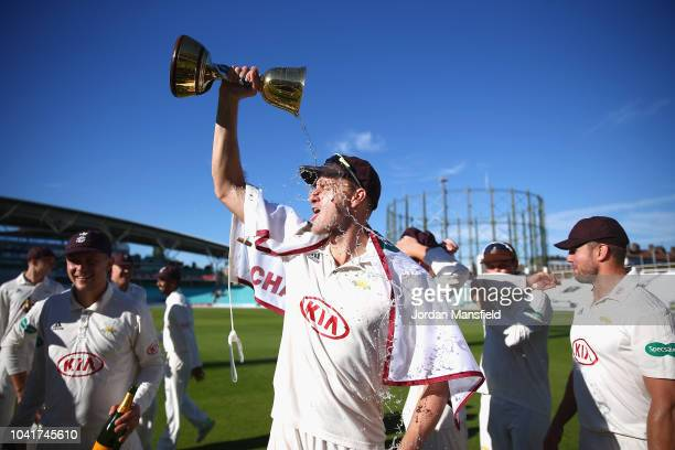 Morne Morkel of Surrey pours champagne over his face with the Specsavers County Championship Division One Cup during Day Four of the Specsavers...