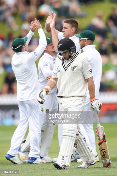 Morne Morkell and Dean Elgar of South Africa celebrate as Tom Latham of New Zealand leaves the field after being dismissed during day three of the...