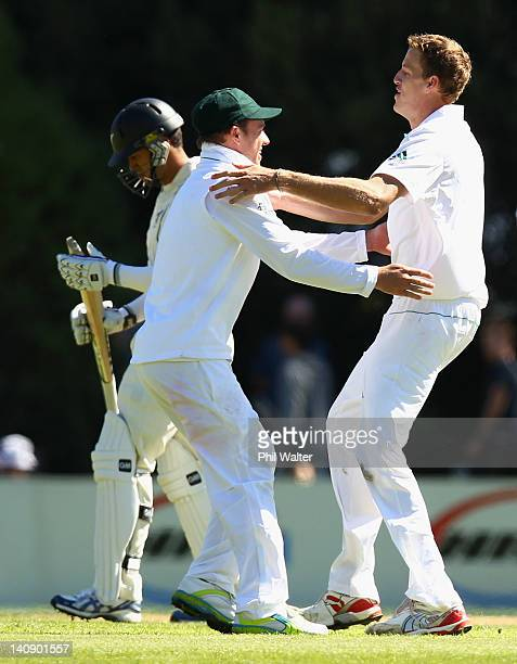Morne Morkle of South Africa celebrates his wicket of Ross Taylor of New Zealand with AB de Villiers during day two of the First Test match between...