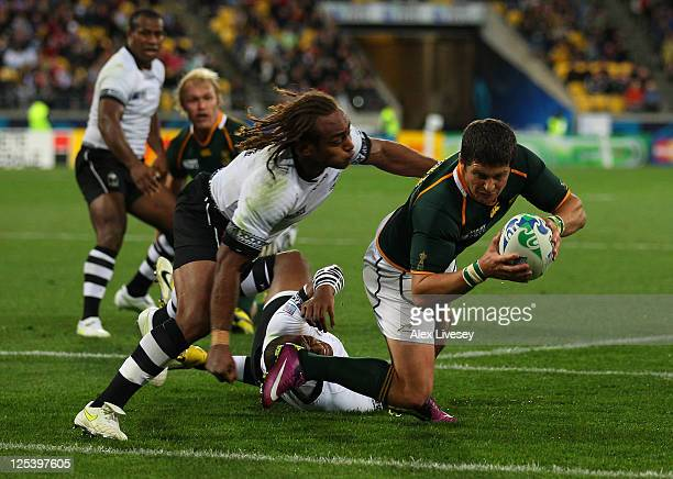 Morne Steyn of the Springboks dives past Gaby Lovobalavu of Fiji to score his team's fourth try during the IRB 2011 Rugby World Cup Pool D match...