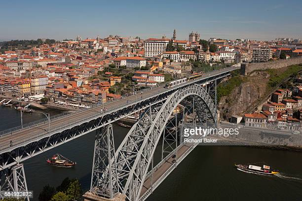 A morning aerial panorama of boats about to pass under while a tram crosses over the Ponte de Dom Luis I bridge with the city of Porto behind on the...