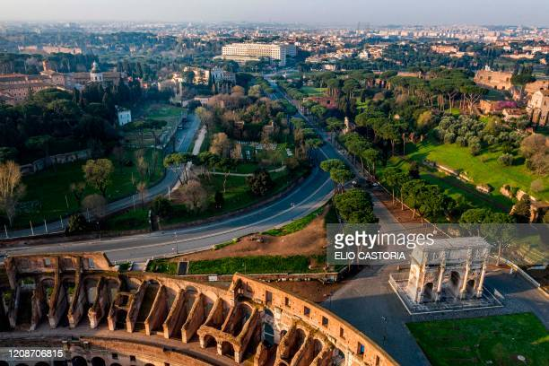 A morning aerial photo taken on March 30 2020 shows deserted streets around the Colosseum monument the Arch of Constantine and Via di San Gregorio...