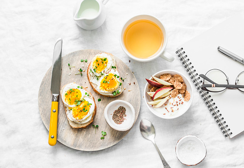Morning breakfast table inspiration - sandwiches with cream cheese and boiled egg, yogurt with apple and flax seeds, herbal detox tea, notebook, glasses on light background, top view. Flat lay 938158976