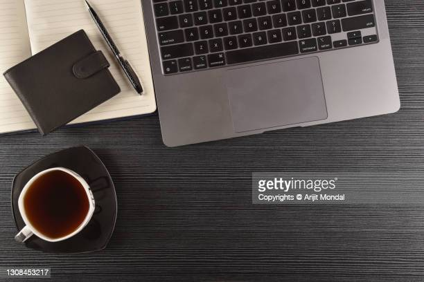 morning coffee, laptop, lather wallet with pen, diary, on table with black background flat lay top view - multimedia stock pictures, royalty-free photos & images