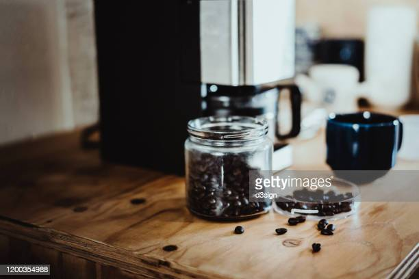 a morning coffee setting with roasted coffee beans, coffee cup and coffee machine in the kitchen counter - 電化製品 ストックフォトと画像