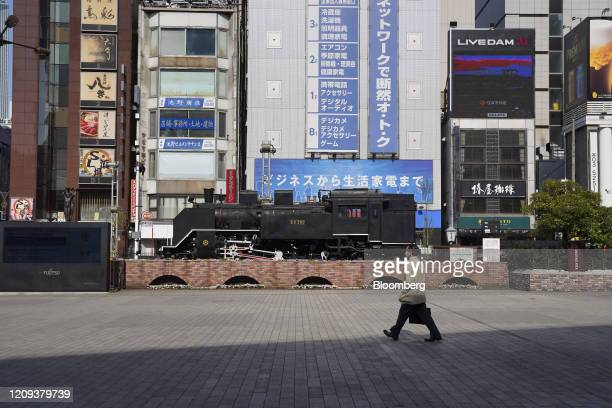 Morning commuter wearing a protective mask walks across the 'Steam Locomotive Square' in front of Shimbashi Station in Tokyo, Japan, on April 8,...