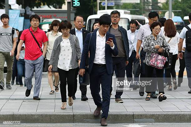 Morning commuters and pedestrians prepare to cross a road at Gwanghwamun square in Seoul South Korea on Friday Aug 28 2015 South Korea is scheduled...