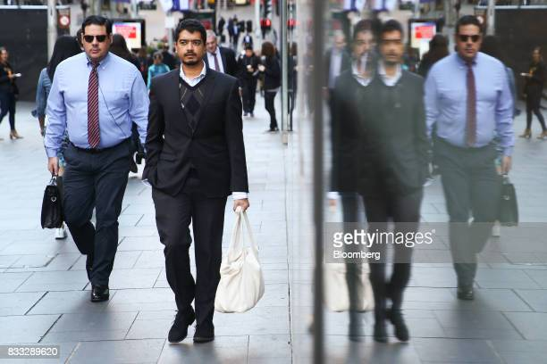 Morning commuters are reflected on a wall as they walk through Martin Place in Sydney Australia on Thursday Aug 17 2017 Australian employers added...