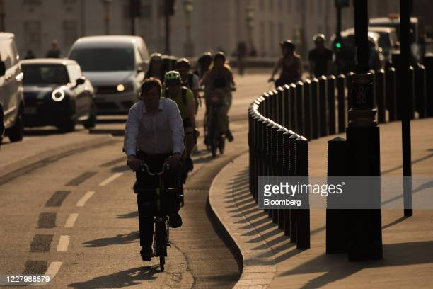Morning commuters cycle beside automobiles in a bicycle lane in London, U.K., on Monday, Aug. 10, 2020. With a budget of £2 billion over the next...