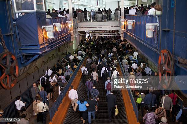 Morning commuters disembark from the Staten Island Ferry June 19, 2012 at the Whitehall Terminal in New York City's financial district. The Staten...