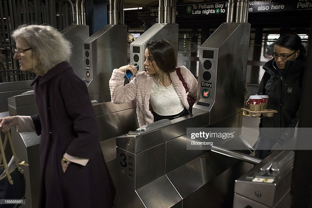 Morning commuters exit a subway turnstile in New York, U.S., on Monday, Nov. 5, 2012. Commuters in New York and New Jersey face gasoline lines and miles of traffic jams as the metropolitan area struggles with the chaos that remains in the wake of superstorm Sandy. Photographer: Scott Eells/Bloomberg via Getty Images
