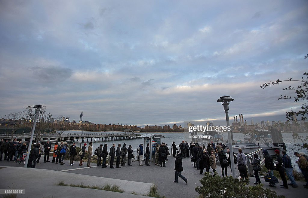 Morning commuters line up to take a Manhattan-bound ferry in the Brooklyn borough of New York, U.S., on Monday, Nov. 5, 2012. Commuters in New York and New Jersey face gasoline lines and miles of traffic jams as the metropolitan area struggles with the chaos that remains in the wake of superstorm Sandy. Photographer: Scott Eells/Bloomberg via Getty Images