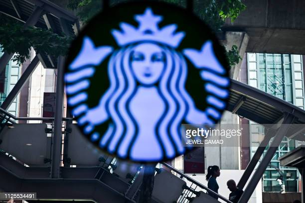Morning commuters make their way on a staircase of a train station passing by a Starbucks logo in Bangkok on February 18 2019