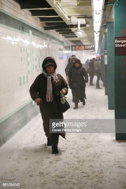 Morning commuters make their way through an underground subway platform covered in snow drifting in from street level grate January 4 2018 in New...