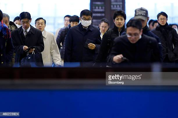 Morning commuters make their way through fare gates at a train station in Inzai Chiba Prefecture Japan on Tuesday Dec 9 2014 Japans recession was...
