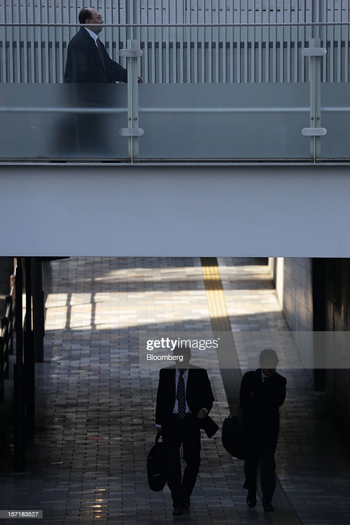 Morning commuters pass under a footbridge in Tokyo, Japan, on Thursday, Nov. 29, 2012. Japan's cabinet approved a second round of fiscal stimulus worth 880 billion yen ($10.7 billion) using budget reserves as Prime Minister Yoshihiko Noda attempts to boost the economy before elections on Dec. 16. Photographer: Kiyoshi Ota/Bloomberg via Getty Images