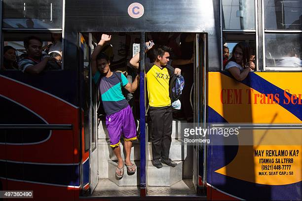 Morning commuters stand in the doorway of a bus in the Makati district of Manila the Philippines on Monday Nov 16 2015 Economic growth in Asia...