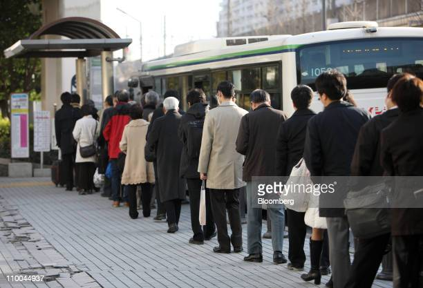 Morning commuters wait in line for a bus outside an East Japan Railways Co train station after Tokyo Electric Co announced the power outages in...