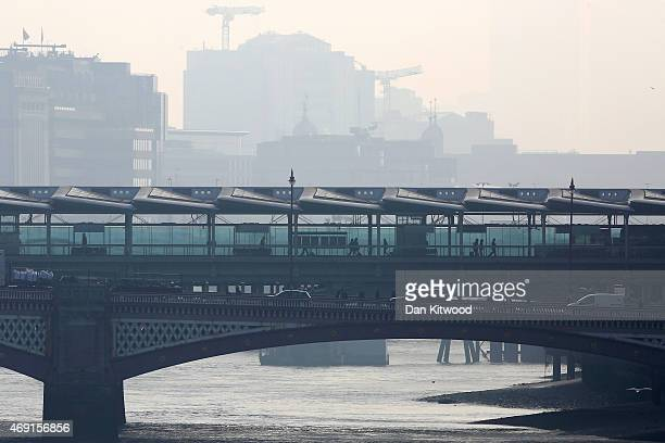 Morning commuters walk across Blackfriars Bridge through smog on April 10 2015 in London England Air pollution and smog has blanketed much of central...