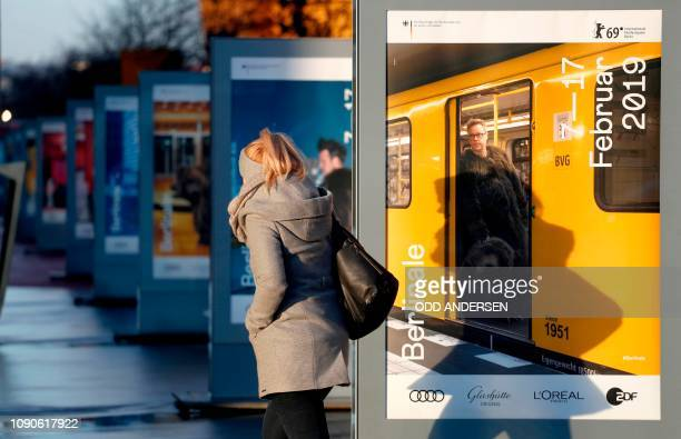 Morning commuters walk past posters announcing the upcoming Berlinale film festival along Potsdamer Strasse in Berlin on Januery 28, 2019. - The 69th...
