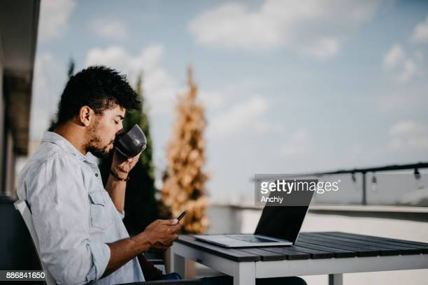 Morning concept of a man drinking coffee on the balcony and using mobile phone.