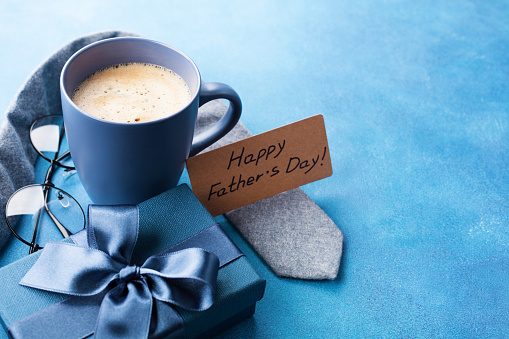 Morning cup of coffee, gift box, necktie and eyeglasses for greeting card on Happy Fathers Day. 950793560
