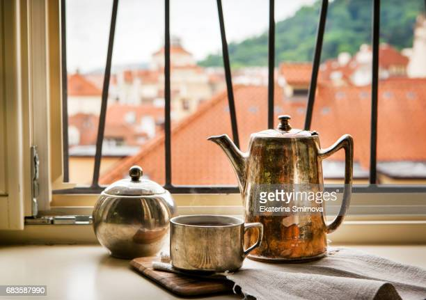 Morning cup of coffee with beautiful view on Prague red roofs from the window
