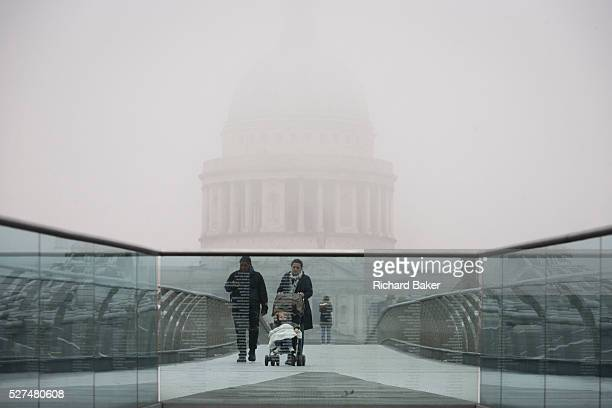 Morning fog envelopes pedestrians crossing the river Thames on the Millennium Bridge with the dome of St Paul's Cathedral in the background. A mother...
