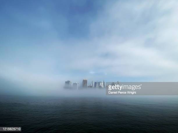 Morning fog lifts over the East River revealing the skyline of lower Manhattan May 27 2020 as seen from Brooklyn Bridge Park Pier 5 in the Brooklyn...