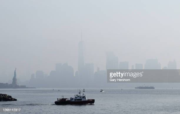 Morning fog shrouds lower Manhattan, One World Trade Center and the Statue of Liberty as the sun rises in New York City on August 9, 2020 as seen...
