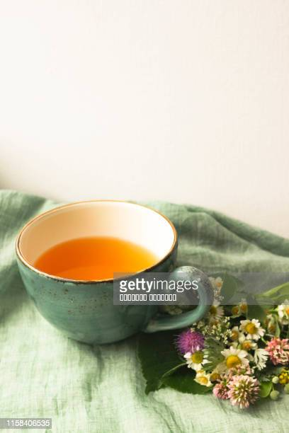Morning herbal tea cup and summer flowers near window view on blue green cotton napkin background.