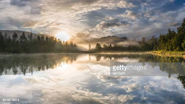 morning mist at lake matheson - reflection lake stock photos and pictures