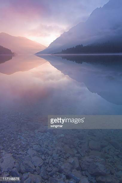 morning mist at lake plansee, tirol, austria, vertical - tranquil scene stock pictures, royalty-free photos & images