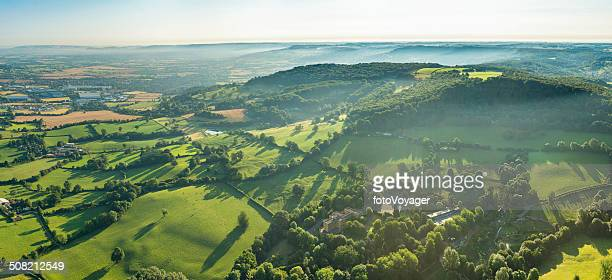 Morning mist swirling through vibrant green summer landscape aerial panorama