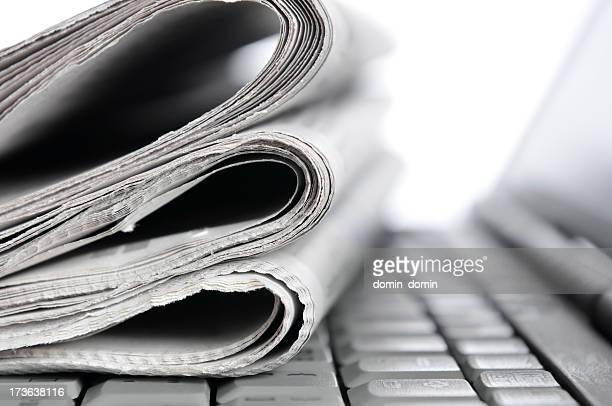 モーニングニュース、折り返し新聞に横たわるノートパソコンのキーボード、モノクロ