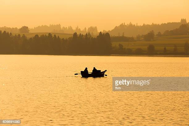 Morning on the lake in a colorful sunrise with a silhouetted rowboat and two fishermen