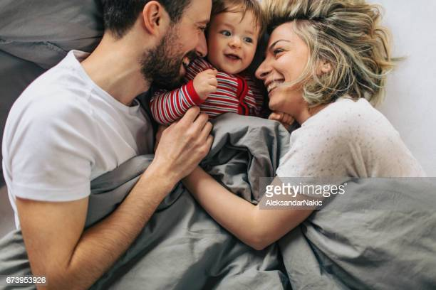 morning routine with our baby boy - couple cuddling in bed stock pictures, royalty-free photos & images