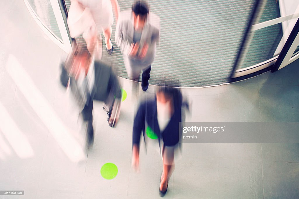Morning rush hour with running business people, entrance : Stock Photo