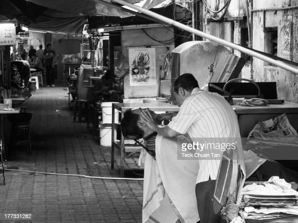 Morning scene of an outdoor shaving service in Petaling Street, Kuala Lumpur, Malaysia.