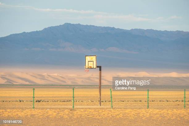 Morning sun rising, shine onto a basketball court in the middle of Gobi desert against the background of a stretch of sand dunes.