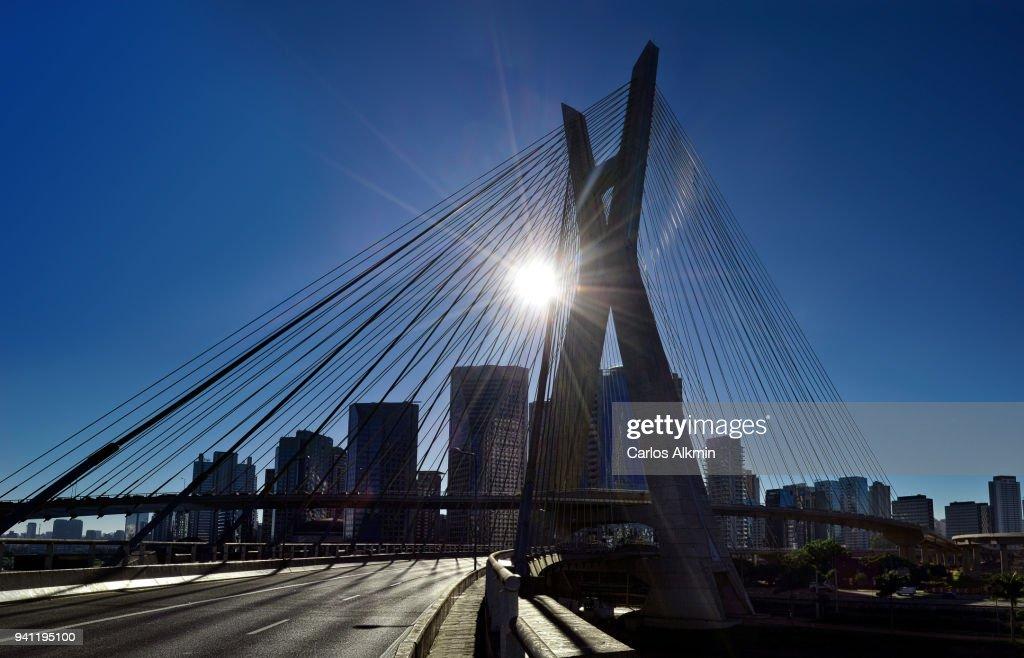 Morning sunbeam behind Octavio Frias de Oliveira Bridge (Ponte Estaiada) with no traffic and Sao Paulo Skyline : Stock Photo