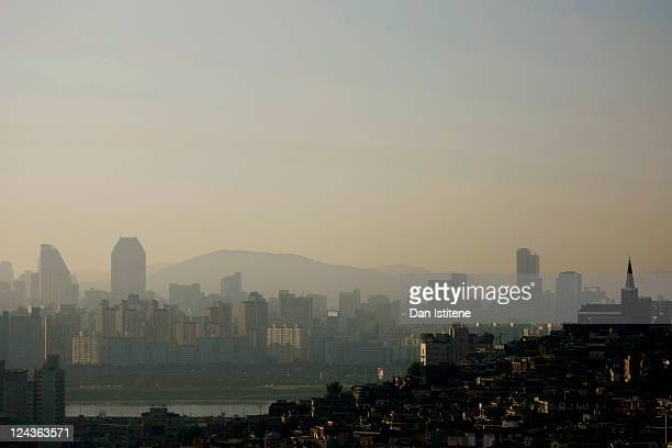 Morning sunlight illuminates residential properties north of the Han River backdropped by mountains and skyscrapers in the Gangnam business district...
