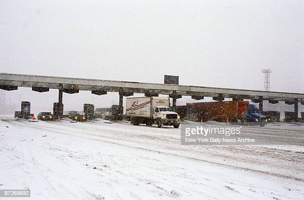 Morning traffic is light moving out of the Exit 16 toll plaza on a snowy New Jersey Turnpike