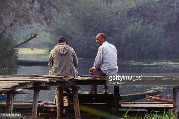 morning view with two men chatting on wooden jetty at traditional floating market. dal lake of kashmir, india. - shaifulzamri stock-fotos und bilder