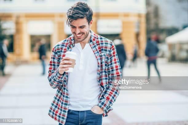 ochtendwandeling met kopje koffie - handen in de zakken stockfoto's en -beelden